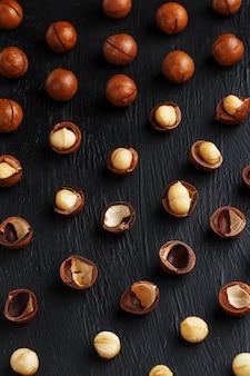 Gereinigt und oberteil wiederholt macadamianüsse auf schwarzem strukturellem steinhintergrund. gesundes essenkonzept