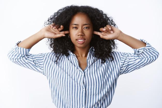 Gereizt satt angepisst wütend afroamerikanerin genervt lautes störendes geräusch zu hören zeigefinger ohrlöcher schielen zähne zusammenkneifen belästigt nachbarn party schmeißen, will polizei rufen