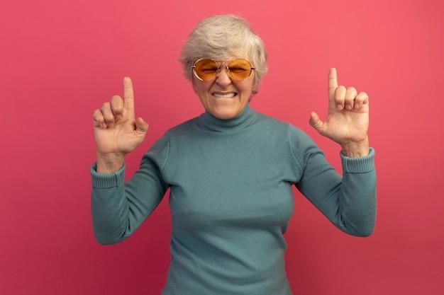 Gereizte alte frau mit blauem rollkragenpullover und sonnenbrille, die auf die lippe beißt, die mit geschlossenen augen isoliert auf rosa wand nach oben zeigt