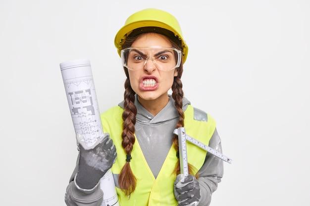 Gereizte baumeisterin presst wütend die zähne zusammen und hält papierplan und maßband beim wiederaufbau der wohnung