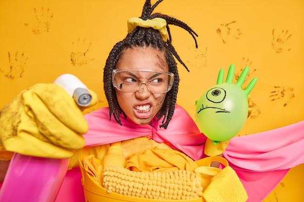 Gereizte dunkelhäutige hausfrau, die superheld ist, reinigt das haus entfernt schmutz, presst die zähne aus ärger zusammen und hält reinigungsmittel isoliert über gelber wand