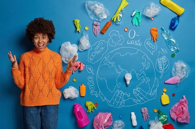 Gereizte dunkelhäutige lockige frau recycelt plastikmüll, schreit vor wut, hält die hände hoch, ist frustriert und verrückt, überwältigt von ökologischen problemen, genervt von umweltverschmutzung