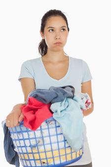 Gereizte frau, die einen korb voll von der wäscherei hält