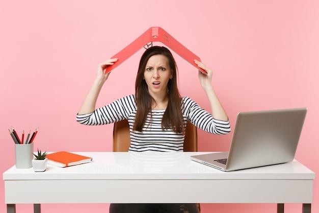 Gereizte frau, die einen roten ordner mit einem papierdokument über dem kopf hält, wie ein dach, das an einem projekt arbeitet, während sie mit laptop im büro sitzt sitting