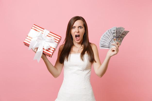 Gereizte frau im weißen kleid, die schreit und bündel viele dollar bargeld rote box mit geschenk hält