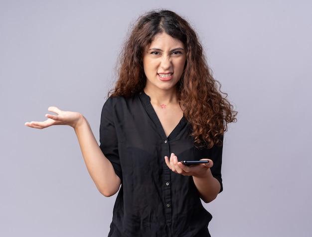 Gereizte junge hübsche kaukasische frau mit handy, die leere hand zeigt