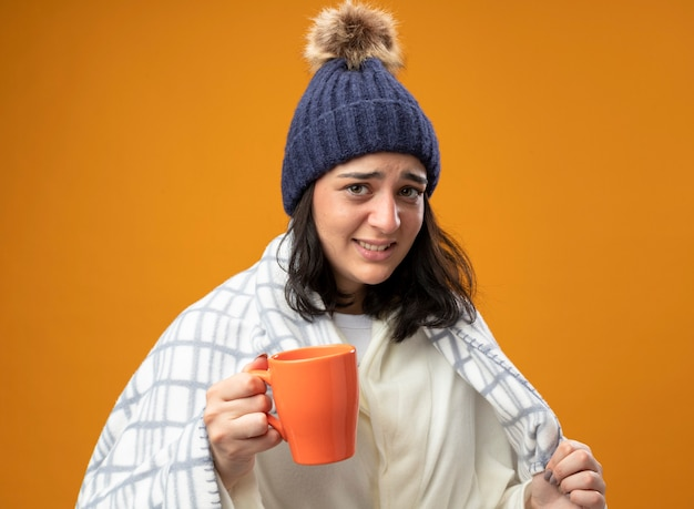 Gereizte junge kranke frau, die robe wintermütze trägt, die in plaid eingewickelt ist, das tasse tee hält, das front ergreifendes plaid lokalisiert auf orange wand betrachtet