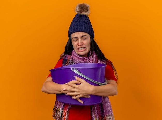 Gereizte junge kranke frau, die wintermütze und schal hält, die plastikeimer mit übelkeit mit geschlossenen augen hält, die auf orange wand lokalisiert sind