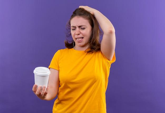 Gereizte junge lässige frau, die plastikkaffeetasse mit hand auf kopf auf lokalisiertem lila raum hält