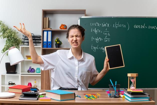 Gereizte junge mathematiklehrerin, die am schreibtisch mit schulmaterial sitzt und eine mini-tafel hält, die leere hand mit geschlossenen augen im klassenzimmer zeigt
