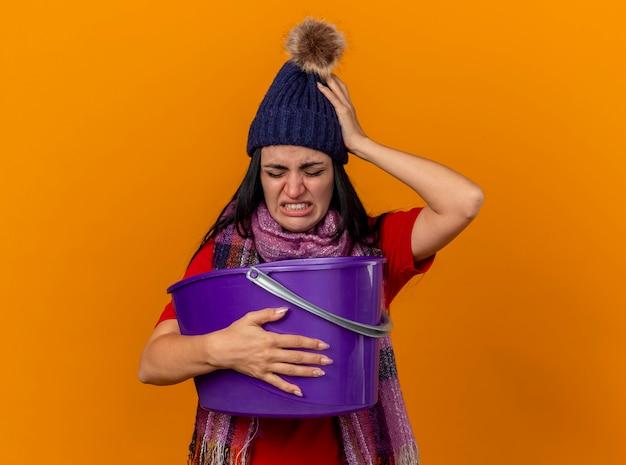 Gereizte und schmerzende junge kranke frau, die wintermütze und schal hält plastikeimer mit übelkeit hält hand auf kopf mit geschlossenen augen lokalisiert auf orange wand hält