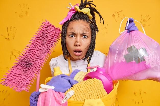 Gereizte unzufriedene frau hat schmutziges gesicht, nachdem sie die hausarbeit satt hat, sammelt müll in der wohnung hält moppständer in der nähe des wäschekorbs, isoliert über gelber wand, schlammige handabdrücke.