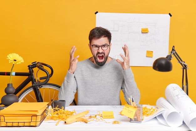 Gereizter bärtiger männlicher unternehmer oder architekt fühlt sich sehr wütend schreit laut hat viel zu tun posen am unordentlichen desktop trägt eine brille arbeitet am startup-projekt drückt negative emotionen aus