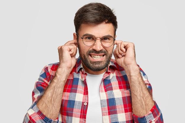 Gereizter bärtiger mann stopft die ohren vor ärger, hört laute geräusche, beißt die zähne zusammen, hat einen unangenehmen gesichtsausdruck, trägt ein modisches hemd und posiert an der weißen wand. hör auf mit diesem geräusch!