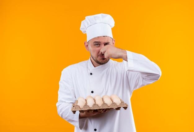 Gereizter junger gutaussehender koch in kochuniform, der eierkarton und seine nase isoliert auf oranger wand hält