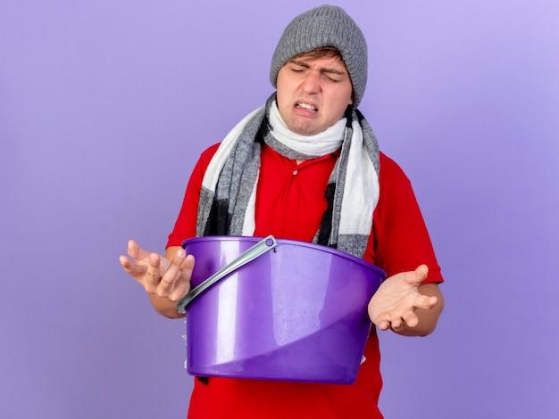 Gereizter junger hübscher blonder kranker mann, der wintermütze und schal hält plastikeimer mit geschlossenen augen lokalisiert auf lila hintergrund mit kopienraum