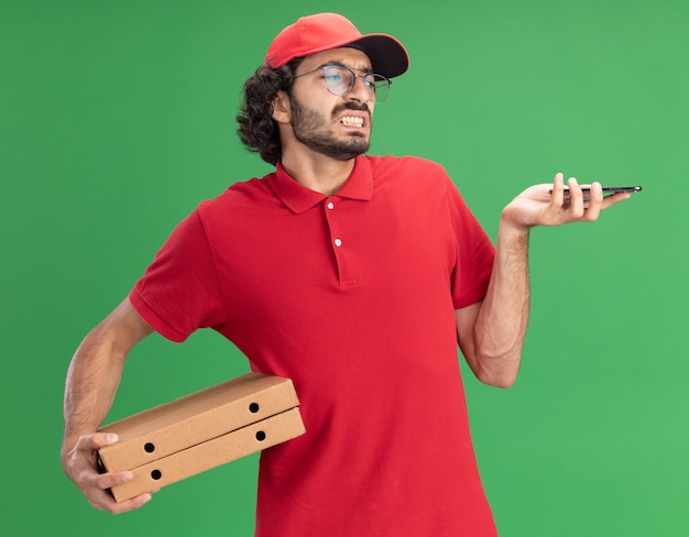 Gereizter junger kaukasischer lieferbote in roter uniform und mütze mit brille, die pizzapakete und handy hält und auf das telefon schaut
