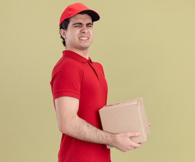 Gereizter junger kaukasischer lieferbote in roter uniform und mütze
