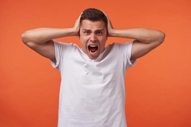 Gereizter junger kurzhaariger mann mit braunen augen, der seine ohren mit erhobenen handflächen bedeckt und den mund offen hält, während er aufgeregt schreit, isoliert über dem orangefarbenen hintergrund