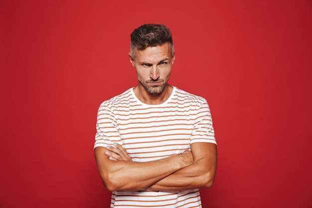Gereizter mann 30er jahre in gestreiftem t-shirt stehend mit verschränkten armen und wütendem blick isoliert auf rot standing
