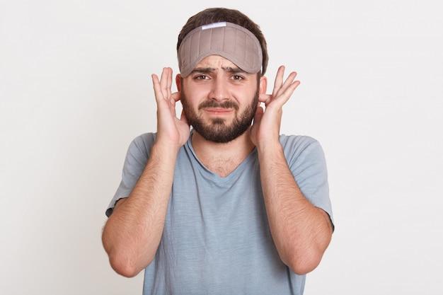 Gereizter wütender junger mann mit bart, der direkt mit den fingern über seine ohren schaut, t-shirt und schlafmaske trägt