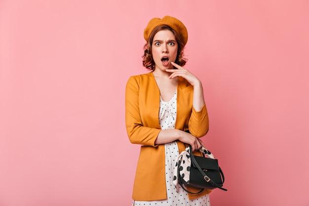 Gereiztes französisches mädchen, das mit offenem mund aufwirft. studioaufnahme der schockierten lockigen frau in baskenmütze lokalisiert auf rosa hintergrund.