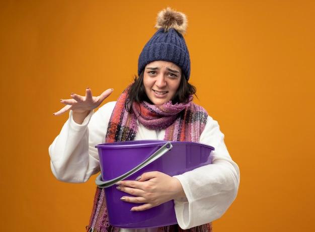 Gereiztes junges kaukasisches krankes mädchen, das robe wintermütze und schal trägt, die übelkeit hält, die plastikeimer hält, die hand in der luft lokalisiert auf orange wand mit kopienraum hält