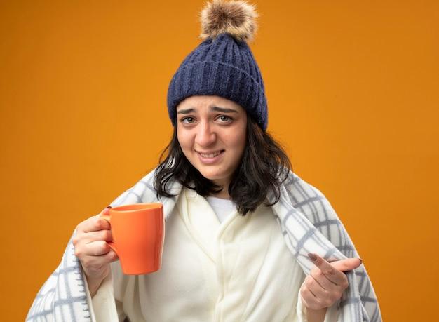 Gereiztes junges kaukasisches krankes mädchen, das robenwintermütze trägt, eingewickelt in plaid, das tasse tee hält und auf kamera lokalisiert auf orangefarbenem hintergrund schaut