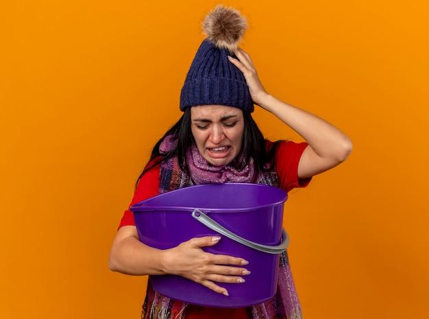 Gereiztes und schmerzendes junges kaukasisches krankes mädchen, das wintermütze und schal hält, das plastikeimer hält, der darin schaut, übelkeit lokalisiert auf orange hintergrund mit kopienraum