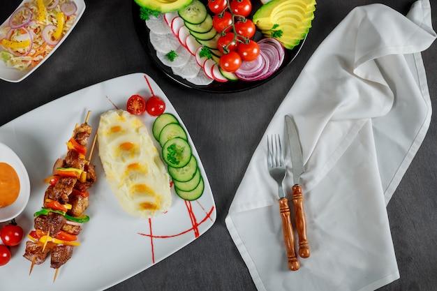 Gericht aus kartoffelpüree, kirschtomaten, gurken und sahniger sauce. gegrillte spieße im restaurant