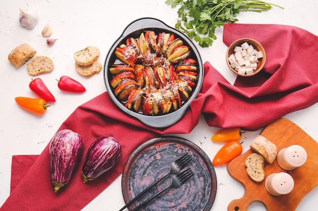 Gericht der leckeren gebackenen auberginen und der tomaten, auf hellem hintergrund