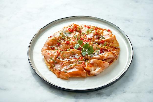 Gericht der mexikanischen küche - tostada mit lachs, süß-saurer sauce, zwiebeln, koriander, serviert in einem weißen teller auf einem marmortisch. nahaufnahme, selektiver fokus
