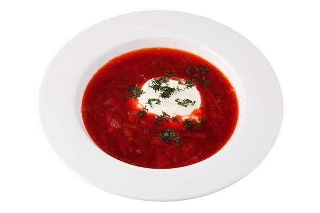 Gericht der russischen und ukrainischen küche, borschtsch mit saurer sahne in der weißen tiefen platte lokalisiert auf weißem hintergrund.