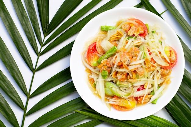 Gericht des würzigen papayasalats auf tropischen palmblättern auf weißer oberfläche