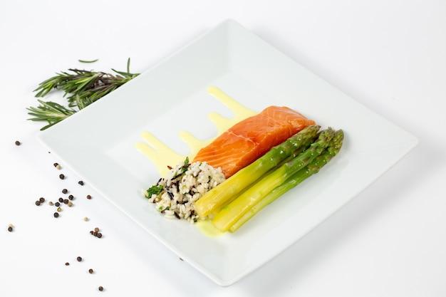 Gericht mit frischem fisch spargel und reis auf dem teller