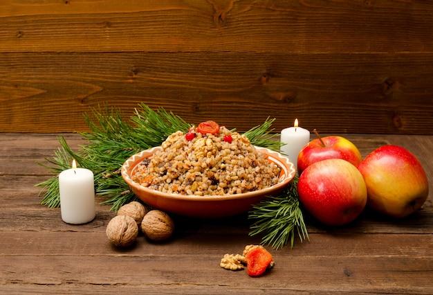 Gericht mit kutia - traditioneller weihnachtsgenuss der slawen am heiligabend. pelz-baumzweig, apfel, kerze auf einem hölzernen hintergrund.