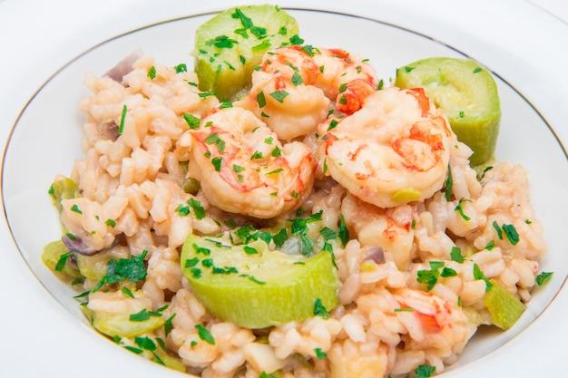 Gericht mit risotto mit garnelen und zucchini