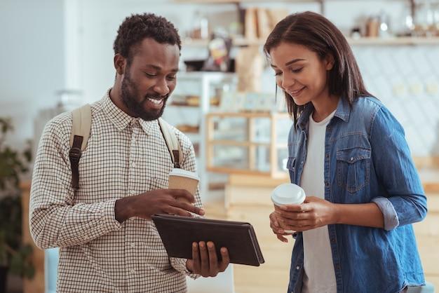 Gerichte auswählen. angenehmer junger mann und sein bester freund, die im kaffeehaus stehen und mit dem tablet das menü des ortes auf ihrer website überprüfen