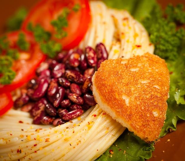 Gerichte für das abendessen ist mit frittiertem brot in form von herzen dekoriert.