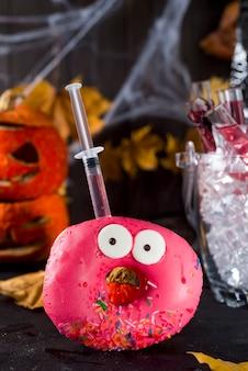 Gerichte mit glasierten donuts, mit einem roten cocktail in einer glasröhre in einem eimer mit eis