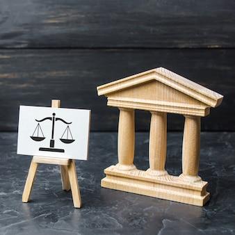 Gerichtsgebäude und ein schild mit waage das konzept des gerichts und der justizjustiz
