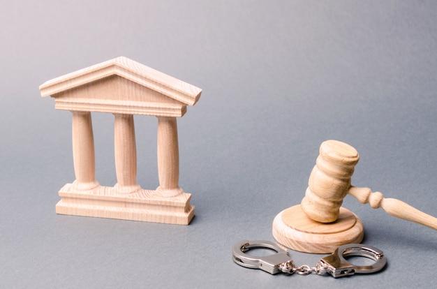 Gerichtsgebäude und handschellen. das konzept des gerichts. urteile in strafsachen. gerechtigkeit.