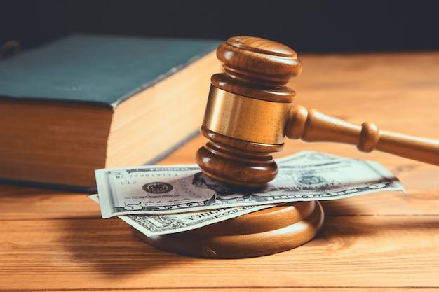 Gerichtshammer mit geld und einem buch auf dem tisch, das ein gesetz kauft