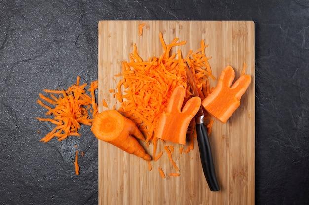 Geriebene karotten auf schneidebrett. der modetrend isst deformiertes und hässliches gemüse. reduzierung von lebensmittelabfällen.