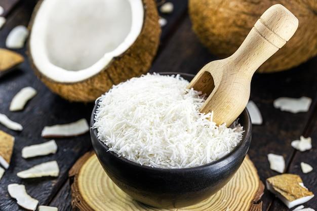 Geriebene kokosnuss in rustikaler steingutschale. kochzutat mit tropischen früchten