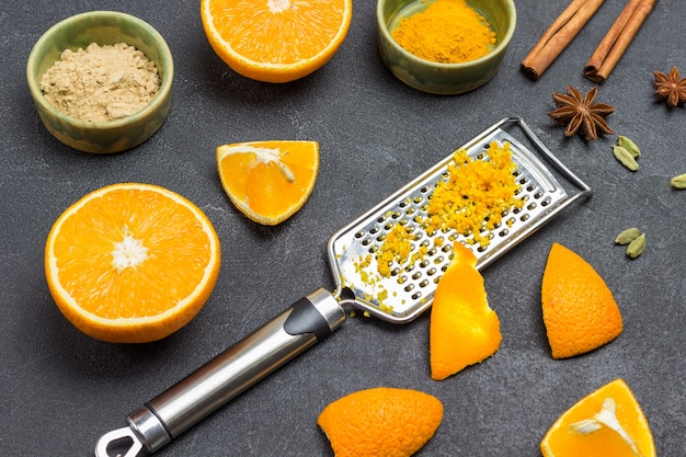 Geriebene schale auf reibe. orangenschale auf reibe. orangenhälften, trockener ingwer und kurkuma, gewürze auf dem tisch. schwarzer hintergrund. ansicht von oben
