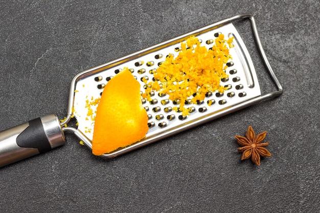 Geriebene schale auf reibe. orangenschale auf reibe. sternanis auf dem tisch. schwarzer hintergrund. ansicht von oben
