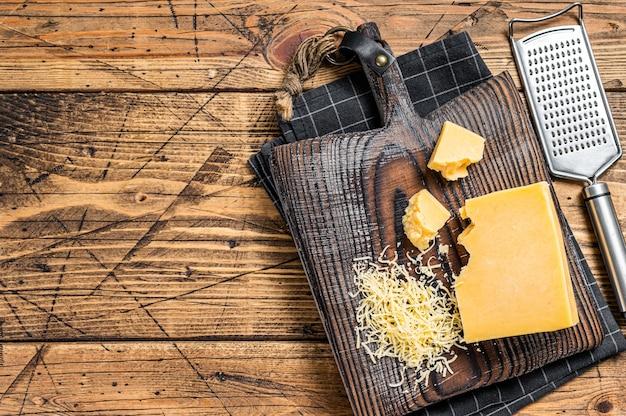 Geriebener cheddar-käse-stück auf einem holzbrett. hölzerner hintergrund. ansicht von oben. platz kopieren.