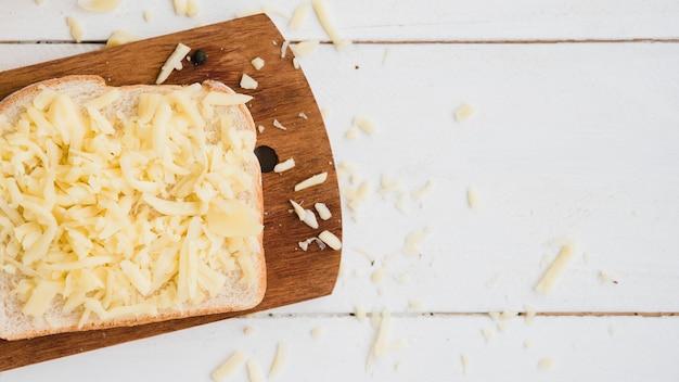 Geriebener käse auf brot über dem schneidebrett auf hölzernem schreibtisch