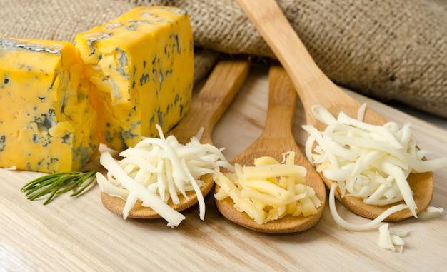 Geriebener käse in holzlöffeln Premium Fotos